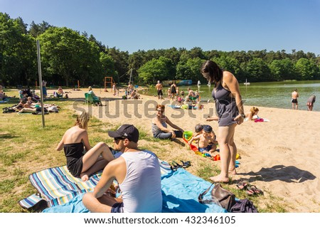 SZCZECIN, POLAND - JUNE 04, 2016: Many unidentified adults and children on sand by a lake on a very warm day - stock photo