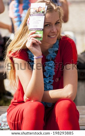SZCZECIN, POLAND - MAY 23, 2014: Juwenalia, is an annual students' holiday in Poland, usually celebrated in late May.Smilling hostess hides her face from the sun.Girl holding a leaflets in hand. - stock photo