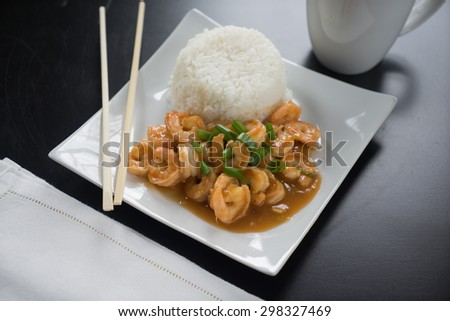 Szechuan Shrimp and rice with green onions on white plate with chopsticks. - stock photo
