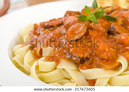 Szekely Gulyas - Hungarian goulash with pork sausage and sour cream on top of pasta and served with a slice of crusty bread.