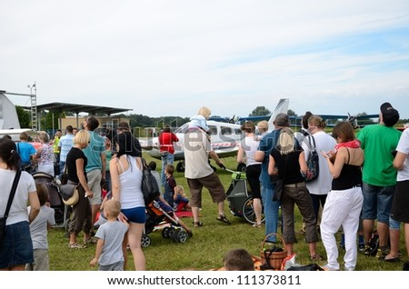 SZYMANOW, POLAND - AUGUST 25: Unidentified group of people admires planes during air show on August 25, 2012 in Szymanow.