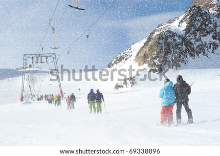 T bar ski lift pulling couple of skiers up the slope. Snowy winter in European Alps.