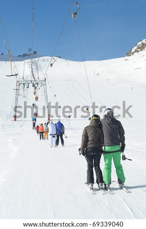 T bar ski lift pulling skiers up the slope. Perfect winter in European Alps. - stock photo