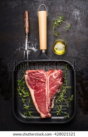 T-bone Steak on frying grill pan with meat fork, oil and seasoning on dark rustic background , top view - stock photo