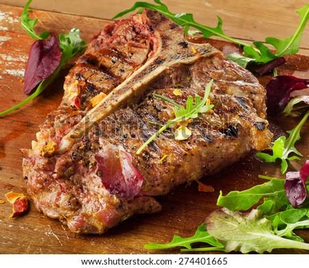 T-Bone Steak with Fresh Herbs on  rustic wooden board - stock photo