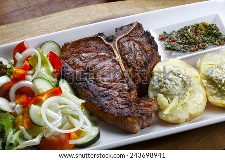 t bone steak with potato salad and vegetables - stock photo