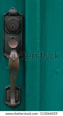 t green door with metal handle - stock photo