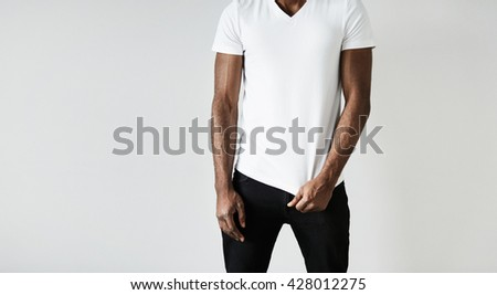 T-shirt design and advertising concept. Cropped shot of young athlete African male model wearing stylish clothes posing against gray wall with copy space for your text or promotional content - stock photo