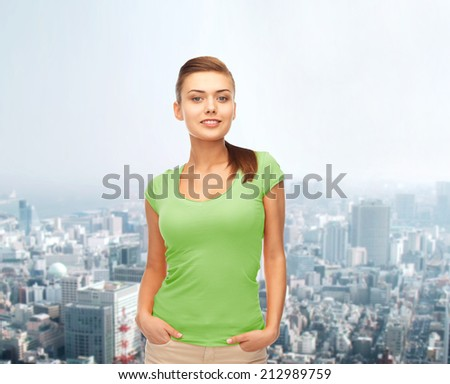 t-shirt design and people concept - smiling young woman in blank green t-shirt - stock photo