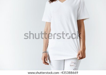 T-shirt design concept. Cropped isolated shot of young brunette casual woman. Close up of slim student girl wearing white copy space T-shirt for your promotional content against white studio wall - stock photo