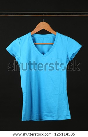 T-shirt on wooden hanger, isolated on black