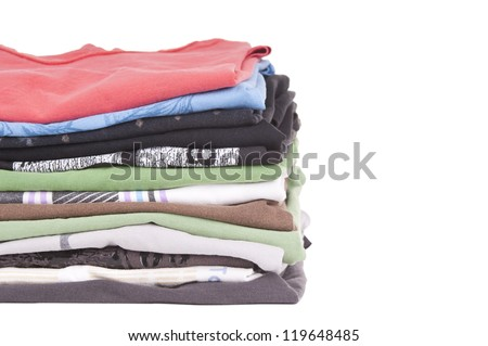 T-Shirts folded and stacked in variety of colors isolated on white - stock photo