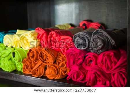 T-shirts stacked on shelves in black. - stock photo
