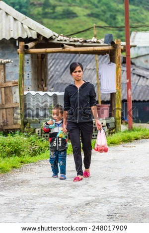 TA PHIN, LAO CAI, VIETNAM - SEP 21, 2014:  Unidentified Red Dao boy goes home with his mother. Red Dao is one of the minority ethnic groups in Vietnam