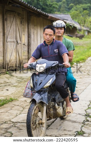 TA PHIN, LAO CAI, VIETNAM - SEP 21, 2014:  Unidentified Red Dao men on a motorbike in the Ta Phin village. Red Dao is one of the minority ethnic groups in Vietnam