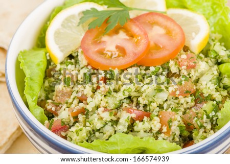 Tabbouleh - Arabic salad made with bulghur wheat, tomato, cucumber, onions, parsley and min and seasoned with lemon juice and olive oil served with pita bread. - stock photo