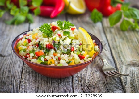 Tabbouleh salad with bulgur, parsley and vegetables - stock photo