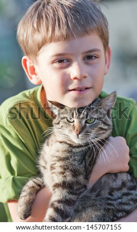 Tabby cat cuddles with nine year old boy - stock photo