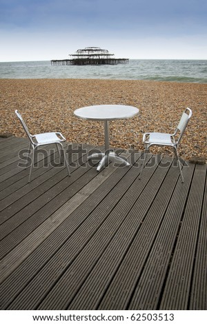 tabel and chairs on wooden decking of outdoor cafe on brighton beach east sussex england