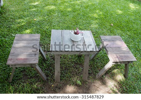 table and chair on a lawn at the garden