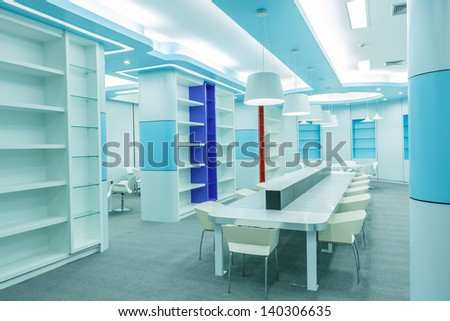 table and chair set with empty book shelf in the empty modern library - stock photo