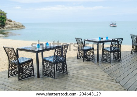 Table and chair setting on the tropical beach with blue sky - stock photo