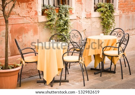table and chairs at a restaurant in italy - stock photo