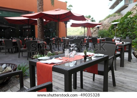 table and chairs in empty restaurant cafe outdoor - stock photo