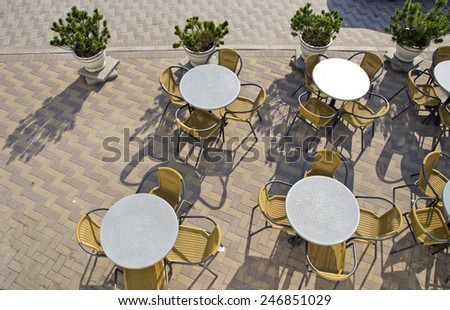 table and chairs in summer city street cafe on pavement - stock photo