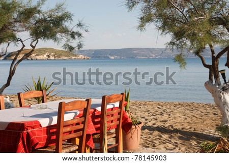 Table and chairs of a Greek taverna at the beach. - stock photo