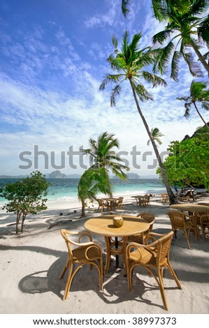 table and chairs on a beautiful beach - stock photo