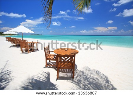 Table and chairs on exotic beach - stock photo
