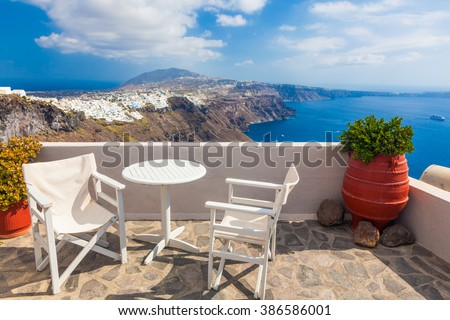 Table and chairs on roof with a panorama view on Santorini island, Greece. Caldera, Aegean sea - stock photo