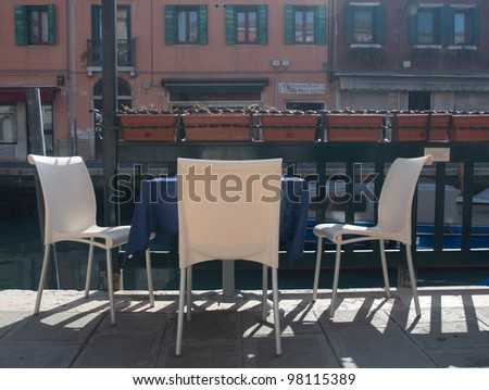 Table and chairs waiting for guests on the street by water canal
