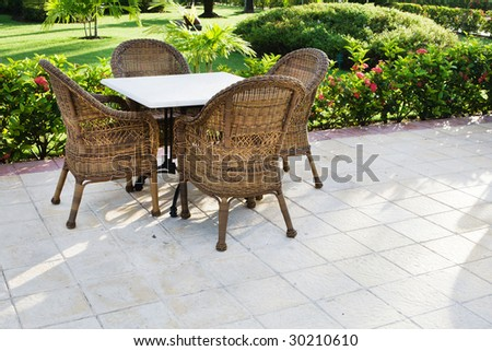 Table and four chairs on patio near bush and grass - stock photo