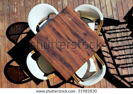 Table and four chairs on wood floor, silhouettes