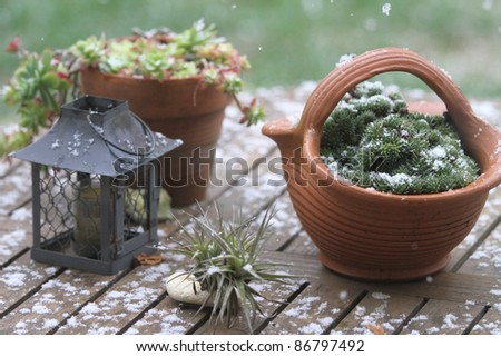 Table and pots covered by snow - stock photo