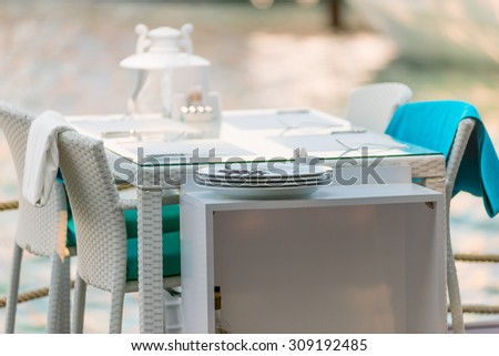 table and white wicker chairs summer cafe - stock photo
