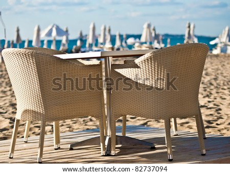 Table and wicker chairs beach cafe. - stock photo