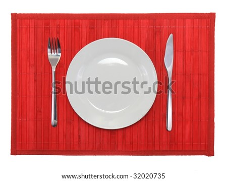 Table appointment-plate,fork,knife,  on  red bamboo mat. All around Isolated.