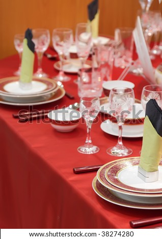 Table appointments on red tablecloth.Accent focus on front. - stock photo