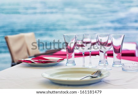 Table at the outdoor sea restaurant, with water on the background