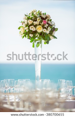 Table centerpiece floral arrangement at luxury event or elegant wedding reception on the beach, in a sunny day - stock photo