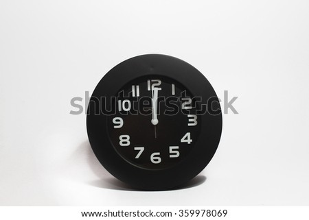 table clock telling time at twelve o'clock, isolated on white background - stock photo