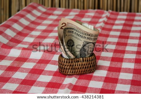 Table cloth and napkin holders with money. On the table  table cloth with reds and whites cubes. Money are dollars. - stock photo