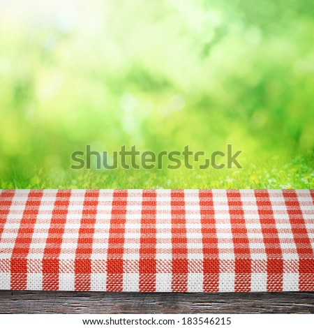 Table cloth and on table for picnic and  sunny summer nature background - stock photo