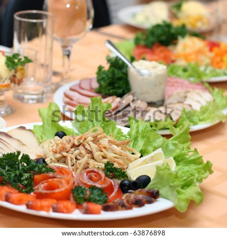 Table covered at restaurant with fish delicacies in the foreground - stock photo