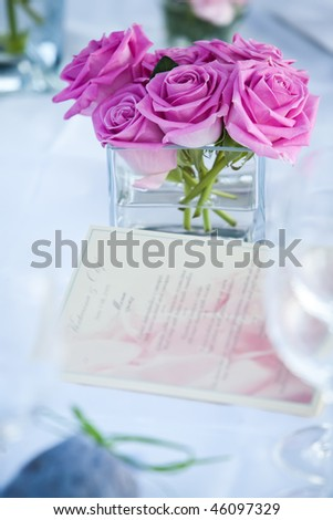Table decor with a menu and pink roses. - stock photo