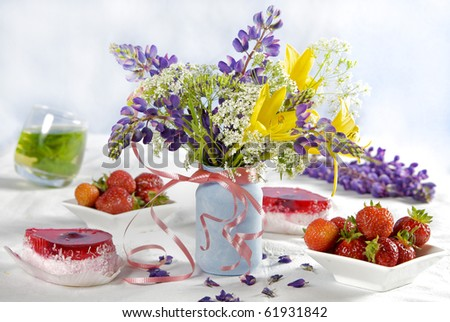 table decor with wild strawberries and flowers - stock photo