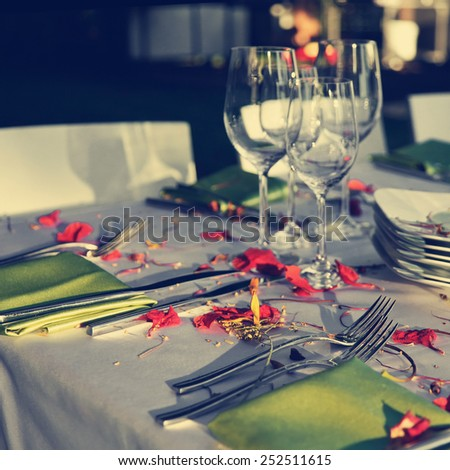 Table decorated for the wedding party covered with beautiful red flowers. Vintage style pictures. - stock photo
